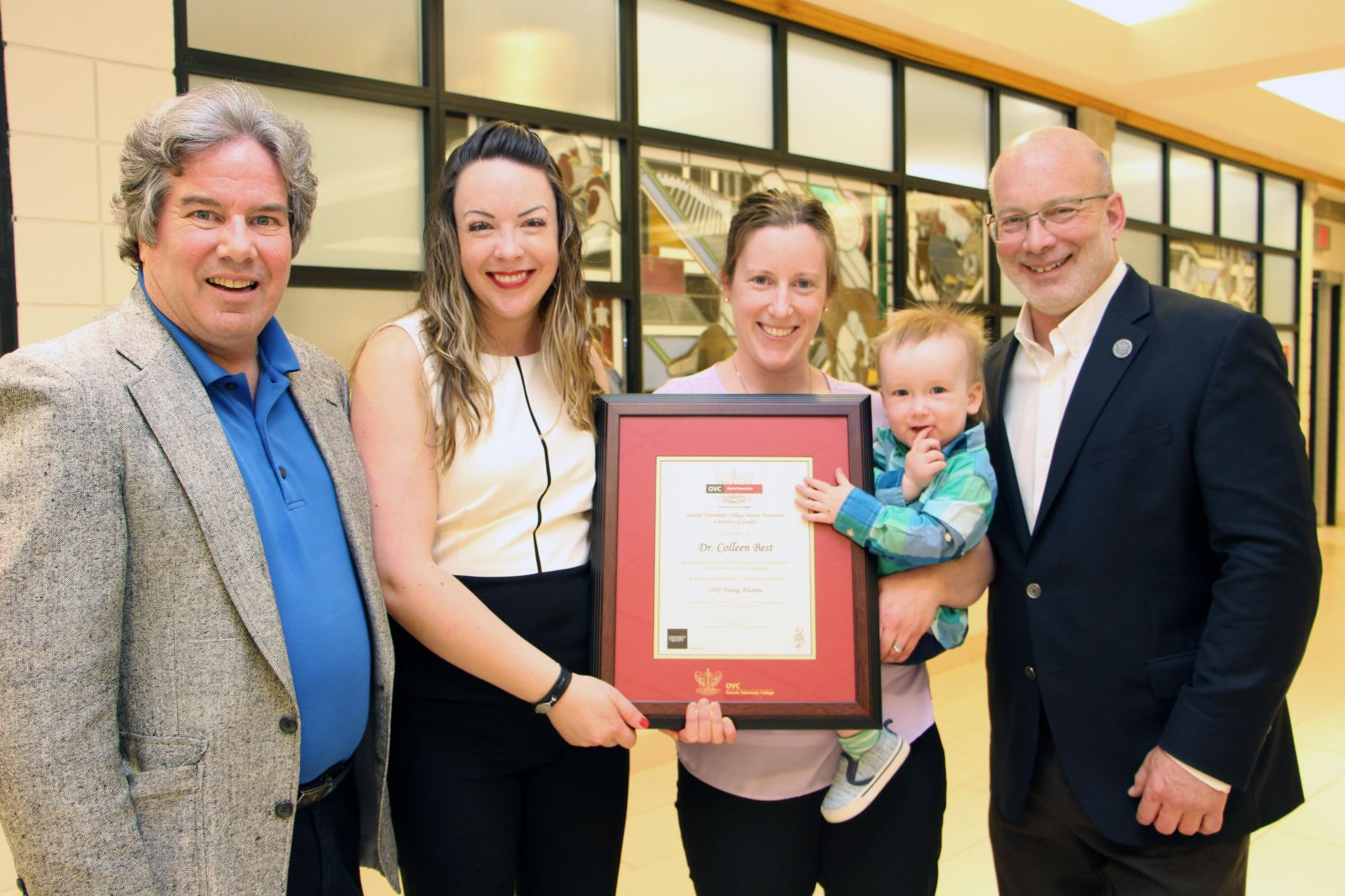 From left, OVCAA president Dr. Paul Woods; Dr. Jackie Parr, OVC DVM 2009; Dr. Colleen Best, OVCAA 2019 Young Alumnus Award winner with her son George; OVC Dean Jeffrey Wichtel.